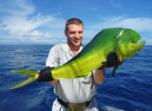 Deep sea fishing, fisherman holding dolphin fish